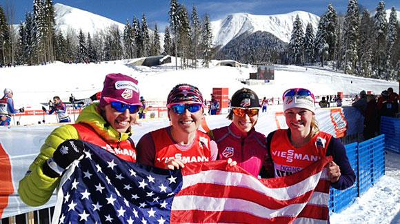 Kikkan Randall, Holly Brooks, Liz Stephen and Jessie Diggins wave the flag to cheer on their teammates in the team sprint at the Laura Cross Country Center outside Sochi. (USSA-Margo Christiansen)