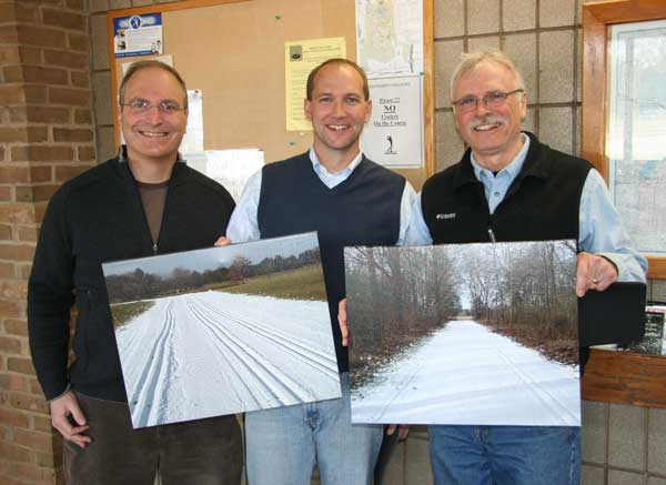 Ken Roth presents custom photos of the Huron Meadows cross country ski trails to Adam Haberkorn and Bill McConnell
