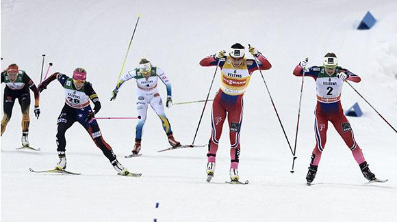 Marit Bjoergen leads out a sprint to the finish as Kikkan Randall (left) gets on the podium for the first time since winning in Lahti a year ago. (Getty Images/AFP-Martti Kainulainen)