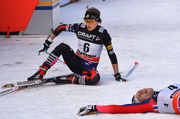 Liz Stephen collapses in the finish after skiing to an historic fifth in the final standings of the Tour de Ski, fourth fastest up the Alpe Cermis. (Getty Images/AFP - Vincento Pinto)